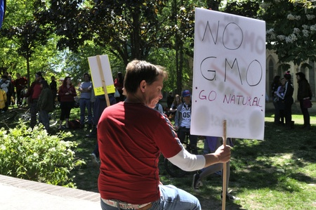 modifying: TORONTO-MAY 25: A man holding a sign asking to reject GMO and have natural food during a rally against GMO giant Monsanto on May 25, 2013 in Toronto, Canada.