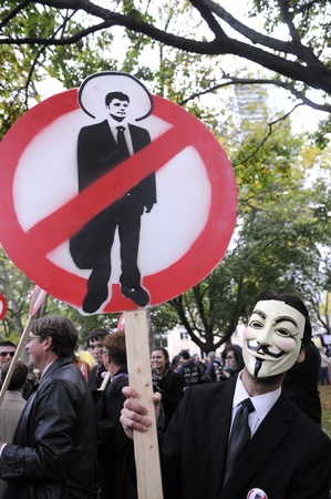 occupy wall street: TORONTO - OCTOBER 15: A demonstrator holding a sign to denounce corporate money laundering during the Occupy Toronto Movement on October 15, 2011 in Toronto, Canada.