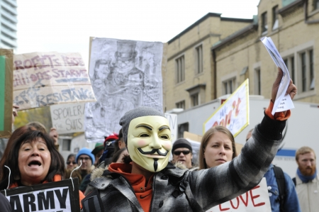 protestors: TORONTO - OCTOBER 17: Angry protestors walking in a rally during the Occupy Toronto Movement on October 17, 2011 in Toronto, Canada.