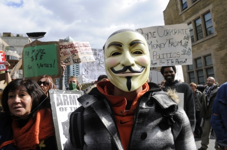 guy fawkes mask: TORONTO - OCTOBER 17: A protestor wearing guy fawkes mask walking in a rally during the Occupy Toronto Movement on October 17, 2011 in Toronto, Canada.