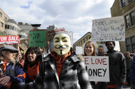 guy fawkes mask: TORONTO - OCTOBER 17: A protestor wearing a guy fawkes mask walking in a rally during the Occupy Toronto Movement on October 17, 2011 in Toronto, Canada. Editorial