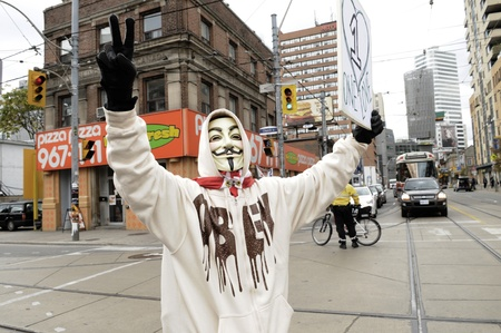occupy wall street: TORONTO - OCTOBER 17: A protestor wearing a guy fawkes mask walking in a rally during the Occupy Toronto Movement on October 17, 2011 in Toronto, Canada. Editorial