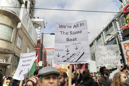 occupy movement: TORONTO - OCTOBER 17: Protestors with placards on yonge and dundas square which says that America,Canada and UK are same, during the Occupy Toronto Movement on October 17, 2011 in Toronto, Canada. Editorial