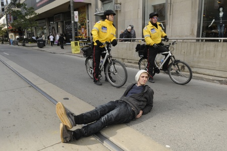 TORONTO - OCTOBER 17: A protestor laying on the street while police keep a close eye on him during the Occupy Toronto Movement on October 17, 2011 in Toronto, Canada.