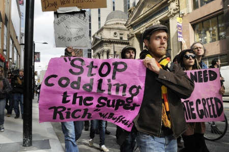 protestor: TORONTO - OCTOBER 17: A protestor walking with a sign with the comment of warren buffet during the Occupy Toronto Movement on October 17, 2011 in Toronto, Canada.