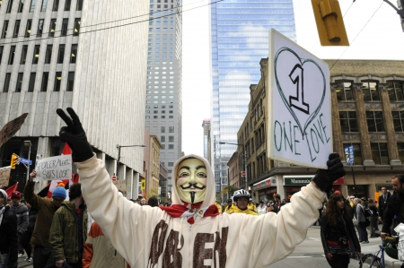 TORONTO - OCTOBER 17: A protestor wearing a guy fawkes mask walking in a rally with placards during the Occupy Toronto Movement on October 17, 2011 in Toronto, Canada.