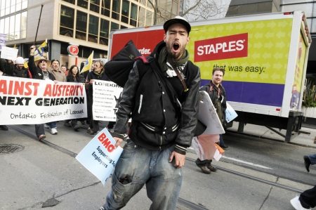 occupy wall street: TORONTO - NOVEMBER 24: An angry protester chanting slogans during a \occupy movement rally in Downtown Toronto on November 24, 2011 in Toronto, Canada.