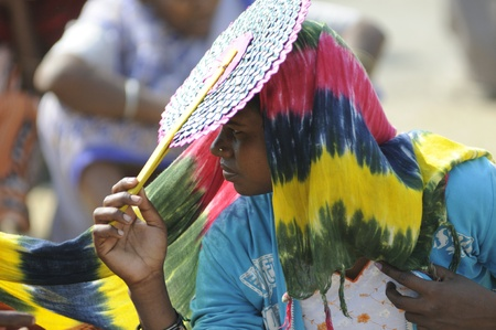 political rally: KOLKATA- FEBRUARY 13: A woman supporter cooling herself with a \\\hand fan\\\ during a political rally in Kolkata, India on February 13, 2011.