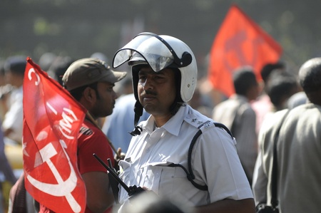 KOLKATA- FEBRUARY 13: A senior traffic constable looks at the approaching crowds, during a political rally in Kolkata, India on February 13, 2011.