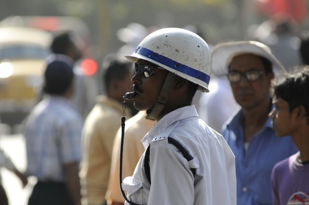 constable: KOLKATA- FEBRUARY 13: A traffic constable blowing his whistle to control the massive crowd, during a political rally in Kolkata, India on February 13, 2011.