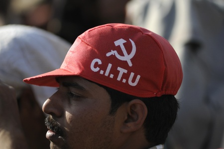 politically: KOLKATA-FEBRUARY 13:A man wearing a red cap of the Trade Union called CITU which is politically attached to the government in West Bengal-during a political rally in Kolkata,India on February 13,2011.