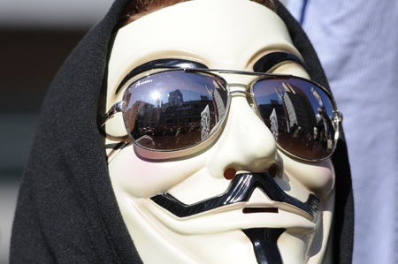 guy fawkes mask: TORONTO - MARCH 11: A guy with a guy fawkes mask listening to the speakers during a protest against an election fraud from last year�?�?s federal election on March 11 2012 in Toronto, Canada. Editorial