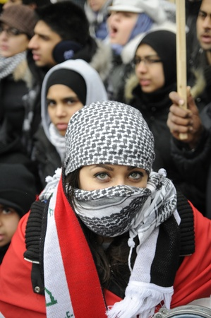 middle east war: TORONTO - JANUARY 10: An Arab girl sharing a look while playing music during a rally to condemn the Israel occupation on Gaza on January 10 2009 in Toronto, Canada.