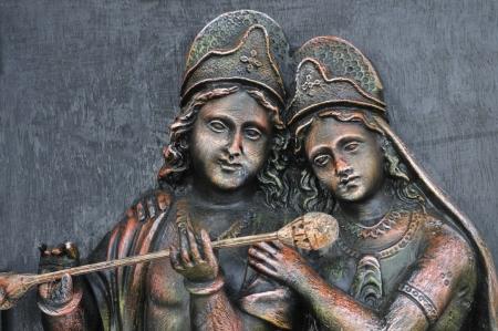 A stone carving of Hindu God Krishna and Hindu Goddesses Radha