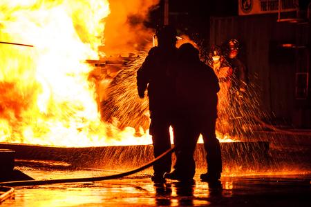 raging: Firemen using water hose on raging fire Stock Photo