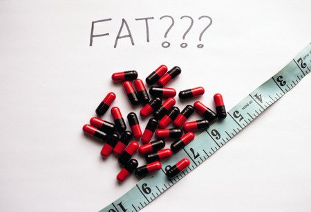 Weight loss concept with fat burner pills and measuring tape Stock Photo