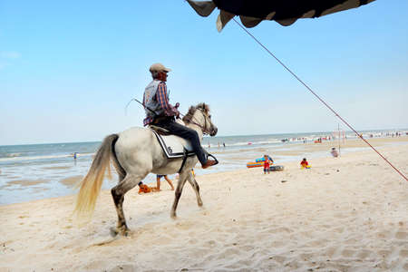 PRACHUAP KHIRI KHAN, THAILAND - APRIL 20, 2018 : Old man riding horse to sandy beach at cha am. Many tourists visit here, View for seascape. Space for text in template.