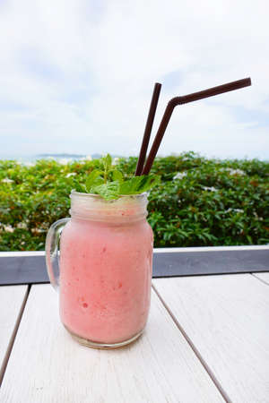 Strawberry smoothie or milkshake in jar with Mint leaves on wooden table. on tree and blue sky background. Summer drink, healthy food. space for your text. Top view Stock Photo