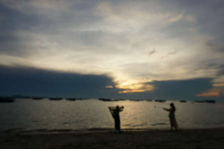 Blurred people having sunset beach in summer vacation as twilight times at Pattaya beach in Thailand. tourists take a photo with sea. View for seascape. Summer holiday and vacation concept for tourism 写真素材