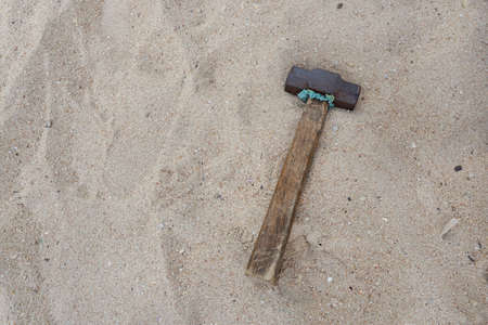 Old hammer with a wooden handle on sand beach background. Space for text in template.
