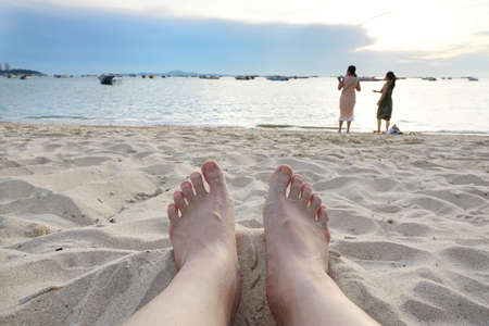 Blurred for background of feet on the beach ,on Silhouette of people having sunset beach in summer vacation as a background, Summer concept, Relax time. Space for text in template. Stock Photo