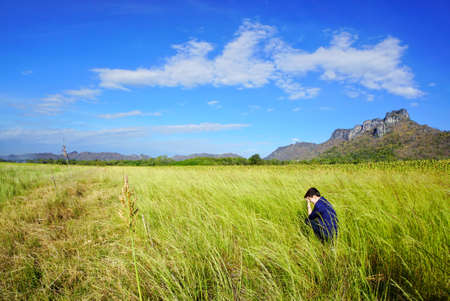 The woman sits holding head with sunflowers field, blue sky, cloud and mountain at Khao Jeen Lae, Lopburi Province in Thailand, space for your text, Many tourists visit here, Tomboy Stock fotó - 106211189