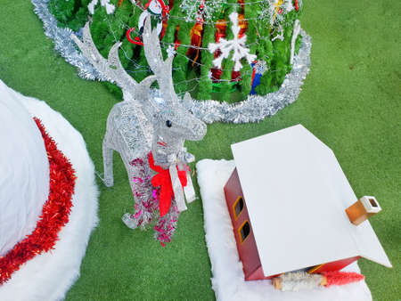 Decorated Christmas with reindeer, tree, home on green grass background, Holiday background, Happy New Year and Xmas