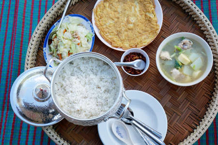 Thai food style, Breakfast set with rice, omelet, Stir fry cabbage, galangal chili paste and minced pork soup on wooden table, Top view