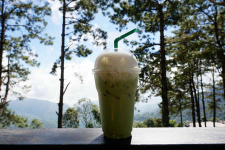 Iced green tea on wooden table on pine tree and sky as a background, Summer drink, healthy food