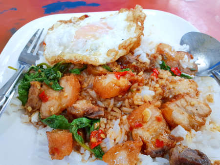 Thai food style, Rice topped with stir fried crispy pork with holy basil leaves and fried egg on white plate, This food is most popular Thai food, Pad kra pao is Thai traditional Foto de archivo