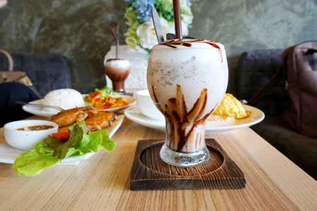 Close up of chocolate frappe coffee with whipped cream on wooden table, Selective focus