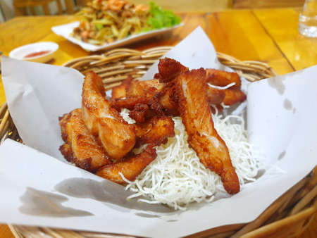 Top view of fried pork sliced and  fried glass noodles in wooden basket on wooden table at restaurant 스톡 콘텐츠