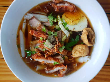 Top view of chinese roll noodle soup with crispy pork, boiled egg and tofu sprinkled with coriander sliced in white bowl on wooden table (Kuayjub, Kuay chap, Kway chap)