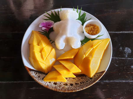 Top view of Thai mango sticky rice topped with coconut cream on wooden table, This food is most popular Thai derrest, Kao neaw ma moung is Thai traditional