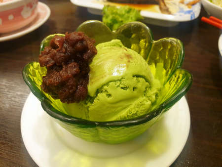Japanese dessert style, Top view of green tea ice cream with red bean topping in green cup on wooden table