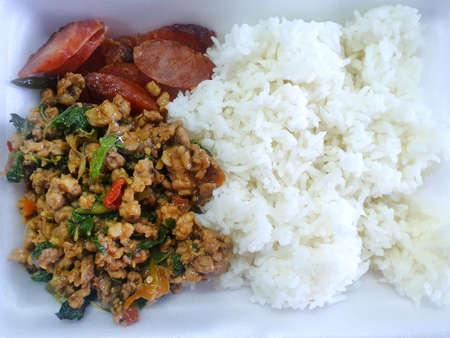 Estilo de comida tailandesa, arroz cubierto con carne de cerdo picada salteada con hojas de albahaca sagrada y salchicha frita en una caja de espuma, esta comida es la comida tailandesa más popular, Pad Kra Pao es tradicional tailandesa