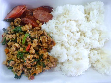Thai food style, Rice topped with stir fried minced pork with holy basil leaves and fried sausage on foam box, This food is most popular Thai food, Pad Kra Pao is Thai traditional