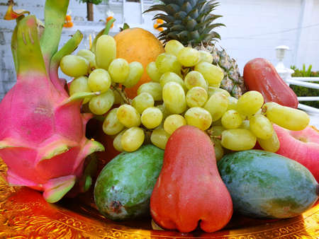 Top view of fresh green grape, rose apple, orange, mango, pineapple, and Dragon fruit in golden plate on blurred background