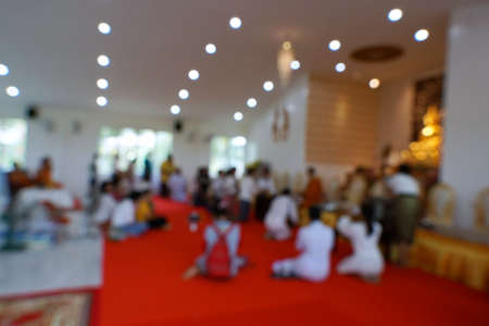 Blurred image of people worshiping Buddha images and monk for sacred blessings in important days of Buddhism in the temple, Religion concept