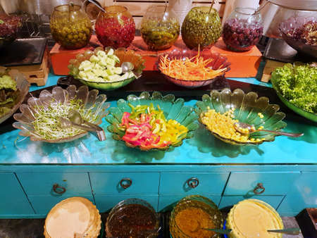 Salad bar, Fresh vegetable with bell peppers, carrot, corn, lettuce, cucumber and ยickled olives in restaurant, Ready to eat, healthy food concept