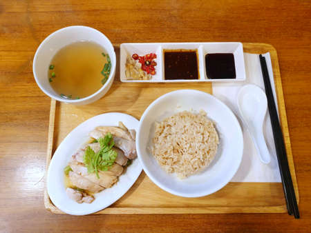 Top view of Steamed chicken with rice, clear soup and bean sauce on tray on wooden table, Hainanese chicken rice set, Khao Man Kai  is Thai traditional, Ready to eat or serve Stockfoto