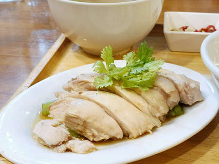 Selective focus of steamed chicken topped with coriander on wooden tray on wooden table, Hainanese chicken rice, Khao Man Kai  is Thai traditional, Ready to eat or serve Stockfoto