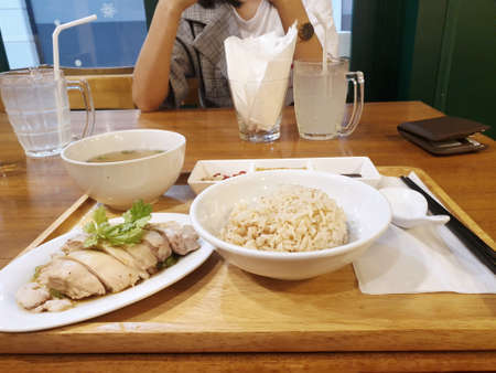 Steamed chicken with rice, clear soup and bean sauce on wooden table in restaurant on blurred woman background, Hainanese chicken rice set, Khao Man Kai  is Thai traditional, Ready to eat