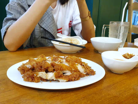 Top view of fried chicken breast in white plate on wooden table in restaurant on blurred woman as a background, Ready to eat