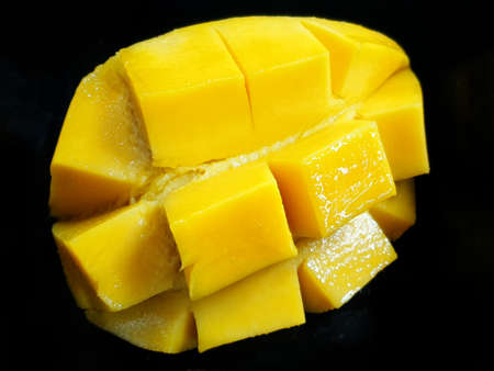 Top view of fresh yellow mango slice isolated on black background, ready to eat or making drinks