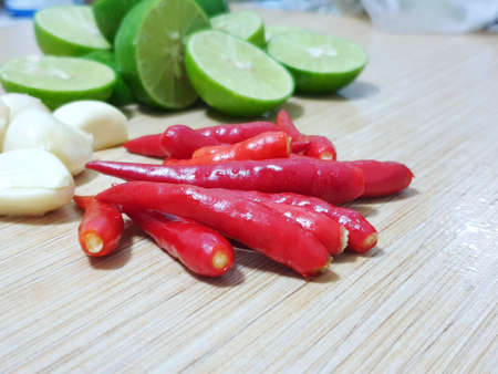 Selective focus of chilli on blurred lemon sliced and garlic on wooden table for cooking, space for your text