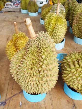 Top view of durian fruit on wooden table for sale in the market, Tropical fruit, copy space (Malvaceae, Durio, Bombacaceae, Phuang Mani), ready to eat, Vertical