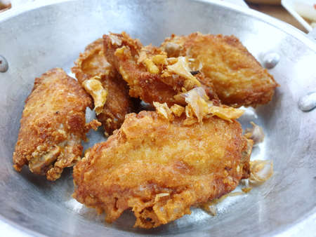 Top view of group fried chicken wings with onions fried on plate as a background in restaurant, ready to eat or serve