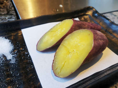 Top view of baked sweet potato with salt on white paper in black plate, Yaki Imo is japanese traditional, Selective focus, Ready to eat or serve 版權商用圖片
