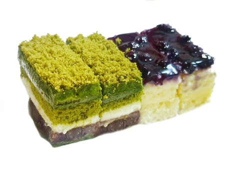 Soft focus of matcha green tea cake on blurred blueberry cheesecake isolated on white background, ready to eat or serve, copy space